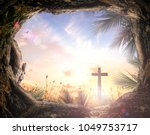 Small photo of Palm Sunday concept: Silhouette cross and empty tombstone with palm leaves over meadow sunset background
