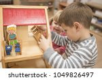 Small photo of Caucasian children plying wiz hwooden toys in kindergarten