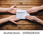 Small photo of Hands pass the white envelope to the other hands on a wooden background. Transfer of money for donation. To send a letter.