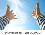 Hands raised up in air across blue sky - stock photo