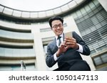 smiling asian businessman in... | Shutterstock . vector #1050147113