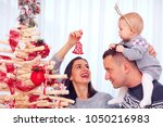 happy young family decorate... | Shutterstock . vector #1050216983