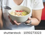 eating healthy breakfast... | Shutterstock . vector #1050273323