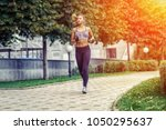a beautiful sporty woman runing ... | Shutterstock . vector #1050295637