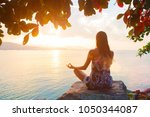 Woman back side meditating sitting on big rock doing yoga in lotus pose under a tree and looking at the sun rays of the sunset, bright rays enlightenment, opening chakras bright colorful concept