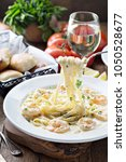 Small photo of Creamy fettuccine alfredo with shrimp on wooden table
