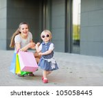 Fashion-monger baby on shopping with mom wear new glasses - stock photo