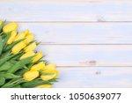 yellow tulips on wooden... | Shutterstock . vector #1050639077