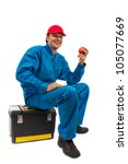 worker sitting on toolbox with red apple in hand - stock photo