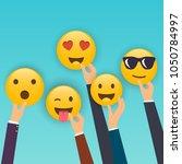 hand holding reaction smileys.... | Shutterstock .eps vector #1050784997