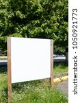 Small photo of Blank sign posted in a parking lot next to the street.