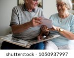 senior couple looking at family ... | Shutterstock . vector #1050937997