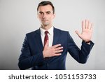 Small photo of Attractive business man taking oath gesture looking serious on gray background