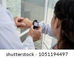 over shoulder view of friendly... | Shutterstock . vector #1051194497