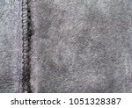 Small photo of Hide skin, gray background, hide cuttings, adipose layer. Natural sheepskin texture. Stitched pieces of leather. Zigzag connecting seam