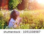a teen blowing seeds from a... | Shutterstock . vector #1051338587