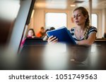 young beautiful student reading ... | Shutterstock . vector #1051749563