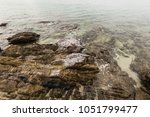 rocks in the sea evening time... | Shutterstock . vector #1051799477