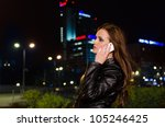 Young brunette woman during phone call in the city centre at night - stock photo