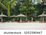 lounge chairs and a sunshade... | Shutterstock . vector #1052580467