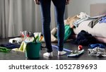 woman horrified by mess left... | Shutterstock . vector #1052789693