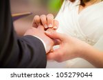 Groom puts ring on brides finger in church - stock photo