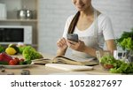 pretty woman reading cooking... | Shutterstock . vector #1052827697
