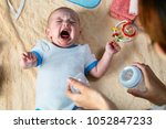 mom soothes crying baby with... | Shutterstock . vector #1052847233