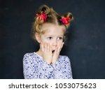 surprised little girl covers... | Shutterstock . vector #1053075623