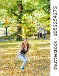 Manhattan New York City NYC Central park, young hipster millennial woman jumping, happy smiling many fallen leaves up in air falling in autumn fall season with yellow foliage