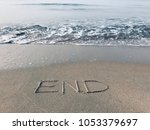 "Small photo of Word ""End"" handwritten on the sandy beach and foamy wave for text of message background. Ending or Beginning concept. Selective focus."