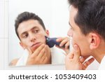 young man in mirror shaving... | Shutterstock . vector #1053409403