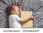 sleeping baby holding a book in ... | Shutterstock . vector #1053666347
