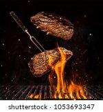 flying beef steaks over flaming ... | Shutterstock . vector #1053693347