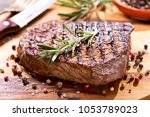 grilled meat with rosemary on... | Shutterstock . vector #1053789023