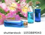 Small photo of Set of blue essential oil tinctures on white wooden table background. Front view. Herbal medicine. Alternative medicine.
