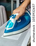 Small photo of Hand on electric iron, ironing in the white shirt.