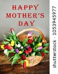 """Small photo of Floral background, greeting card, harvesting, mocap With the inscription: """"Happy mothers day"""": bouquet of colorful tulips in basket on wooden background, copyspace"""