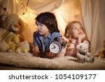 Small photo of Kids holding in hand clock. Alarm indicates late time. They are felling chagrin. Boy and girl in beautiful tent in playroom