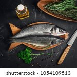 Small photo of Fresh raw trout fish trout, knife for cutting. Ingredients for raw trout fish are pepper, herb thyme, rosemary, parsley, olive oil. Dark background. Top view.