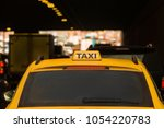 yellow taxi moves in the midst... | Shutterstock . vector #1054220783