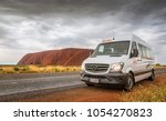 Small photo of Ayers Rock, AUSTRALIA - Sep 29, 2017: Uluru-Kata Tjuta National Park. Rented campervan Apollo driving along a bitumen road around Uluru (Ayers Rock), Top Australian Tourist Destination and Aboriginal