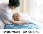 asian nurse in elderly care... | Shutterstock . vector #1054316243