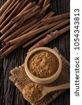 Small photo of cinnamon and cinnamon powder on wooden background