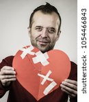 Small photo of Healed love. Valentines Day concept. Adult smiling man holding big red heart with plaster. Male healing relationship.