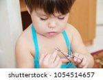 little girl cutting fingernails ... | Shutterstock . vector #1054514657
