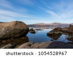 A low perspective view over a rocky beach leading to Loch Lomond and the mountains beyond