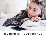 disappointed sad girl lying on... | Shutterstock . vector #1054556423