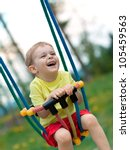 Cute baby boy playing on swing in spring park - stock photo