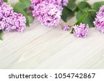 lilac flowers on wooden table... | Shutterstock . vector #1054742867